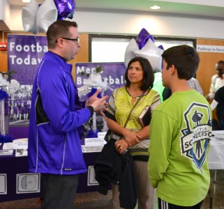 Pioneer's Jason Skiba talks to a mother and son from Holland, Michigan about the many perks of attending Pioneer High School. Photo and slide show by Jo Mathis.