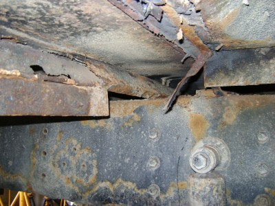 A body cross member is rusting away.