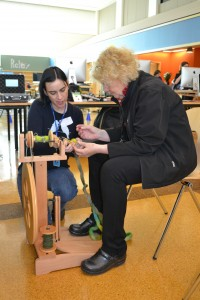 Anne Drozd of the Ann Arbor District Library shows Sara   how to spin.