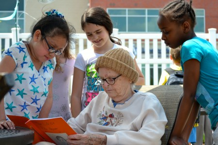 Rita    reads the biography the students wrote about her after they interviewed her on a previous visit.