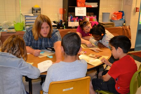 Brendan Hatt, a fifth grade teacher at Pattengill Elementary, helps a small group with reading comprehension.