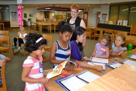 Camp Director Eileen Bigham checks on students at one of the several writing camps.