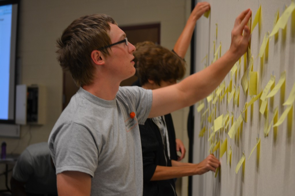 Trevor Wells adds his Post-it note to the wall of students' interests.