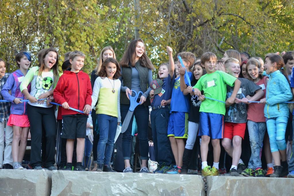 Stephen's classmates help his sister, Alexa, cut the ribbon of the new amphitheater.