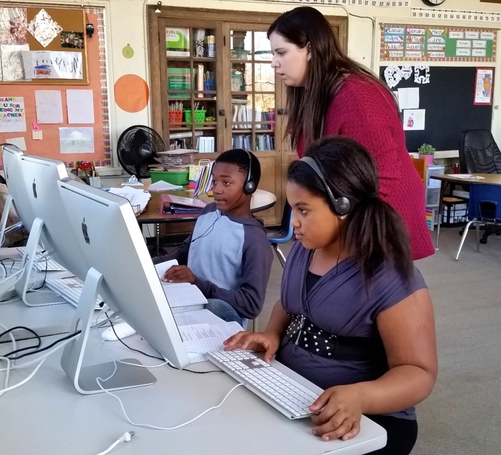 MSU grad student , who is earning a master's in special education and interning at Burns Park Elementary, helps two fifth graders with ...