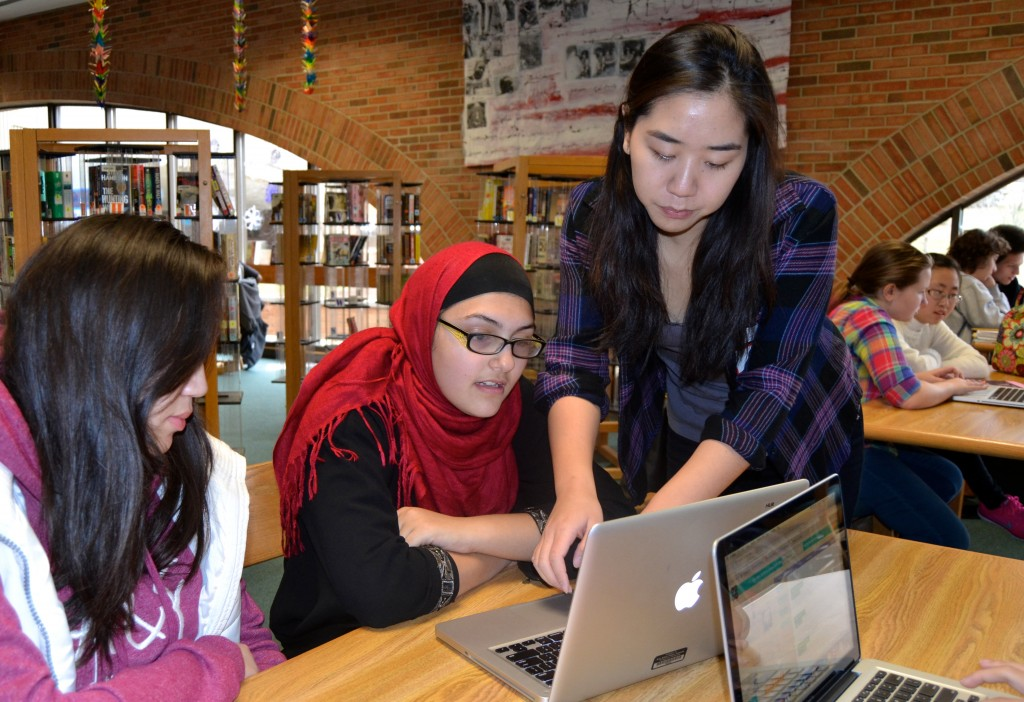 Rosa Wu (Huron High School class of '13) helps Huron freshmen learn to program during Hour of Code Wednesday.