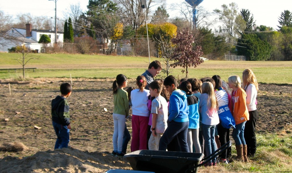 Jim Vallem, land steward at Thurston Nature Center, helps the students plant seeds for the prairie.