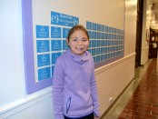 Hailey    stands by the Wonder Wall at Burns Park Elementary