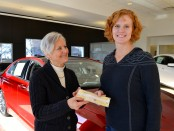 Moira   , right, accepts a check for $15,000 from Sesi Lincoln Mercury. Because she has a large family more suited for the family van, Sesi agreed to give her the check instead of a two-year lease for the car behind her.