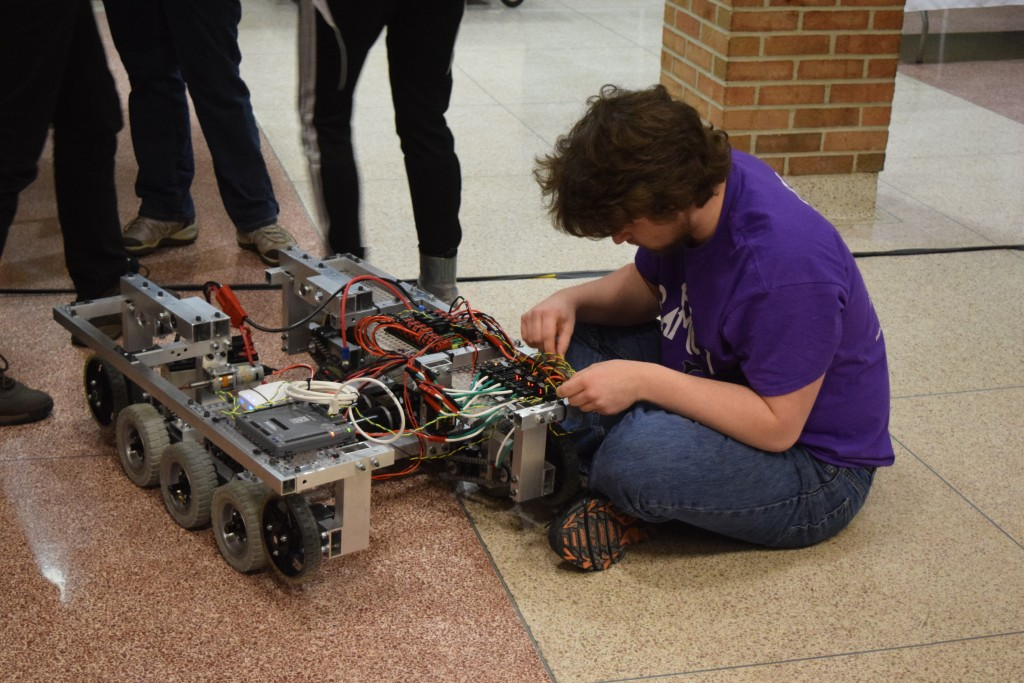 A member of the Pi Hi Samauri team makes adjustments on their robot.