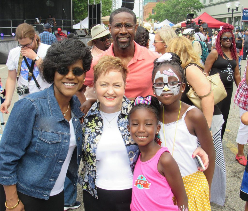Ann Arbor School Board Trustee Simone Lightfoot, Superintendent Jeanice Swift and Pioneer High School Class Principal Kevin Hudson with kids at the 2016 African American Downtown Festival.