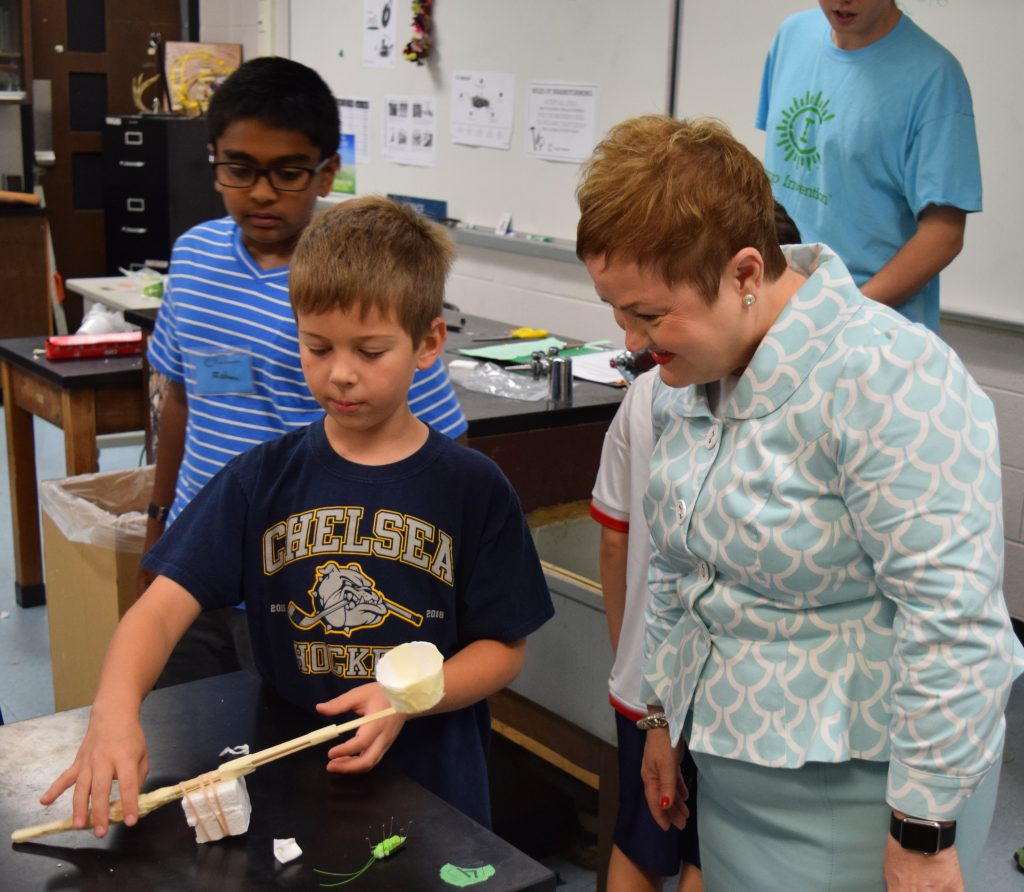 A student in Camp Invention discusses the catapult his team made with AAPS Superintendent Jeanice Swift.