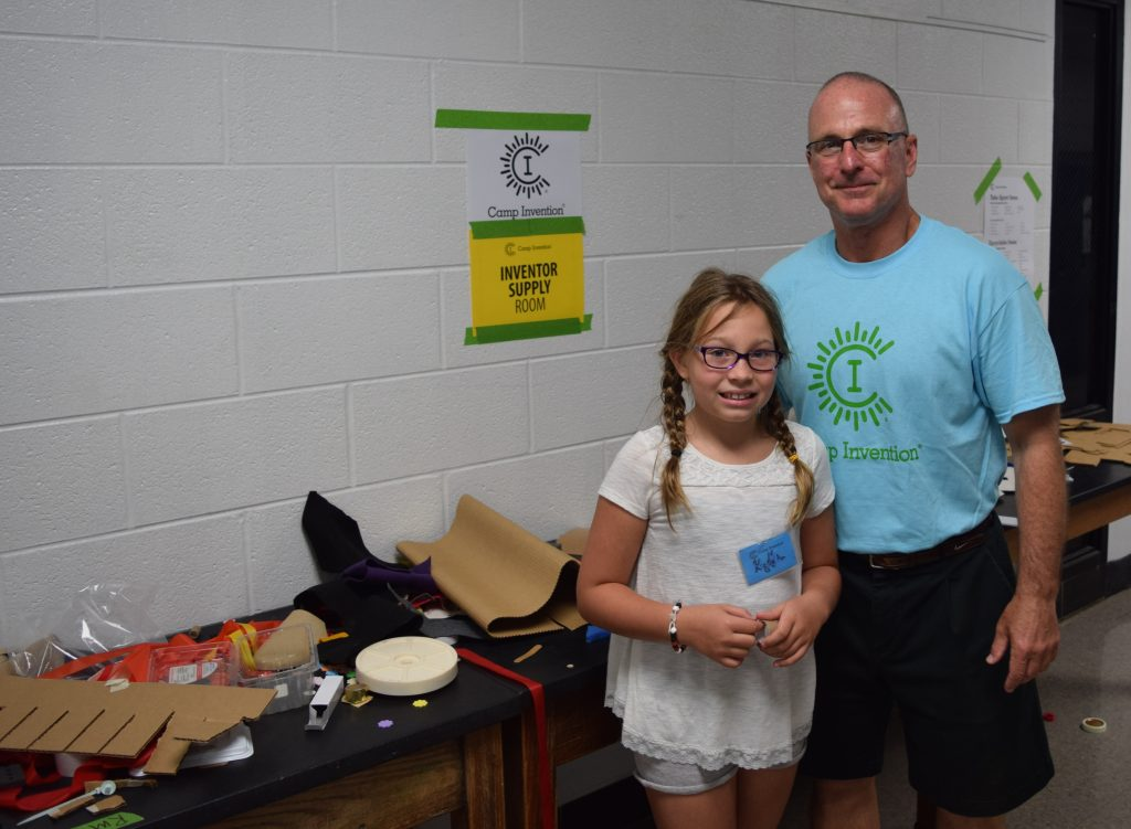 Camp Invention Thomas Hill and a camper next to the supply table students use for their projects.