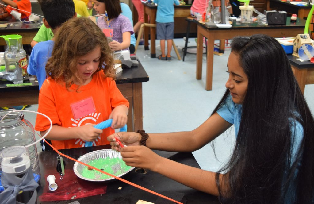 A Camp Invention student and a high school volunteer work on the design for a theme park.