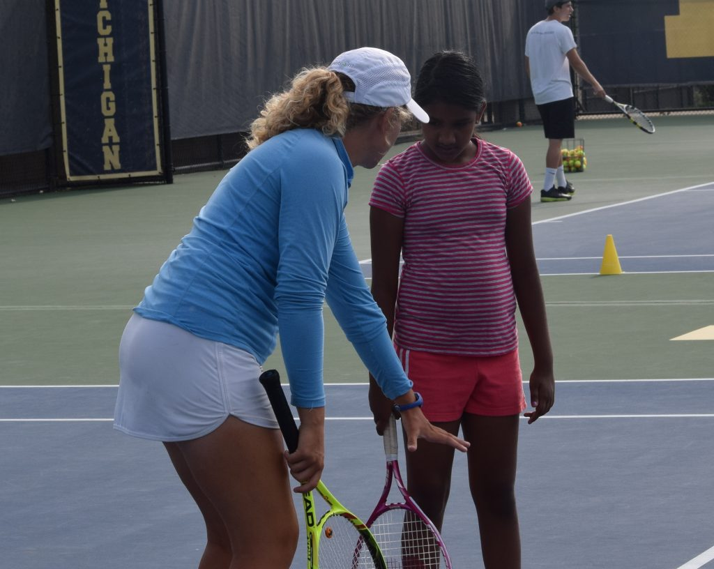 Youth Tennis Coordinator Zofii Casterline gives pointers to a young camp member.