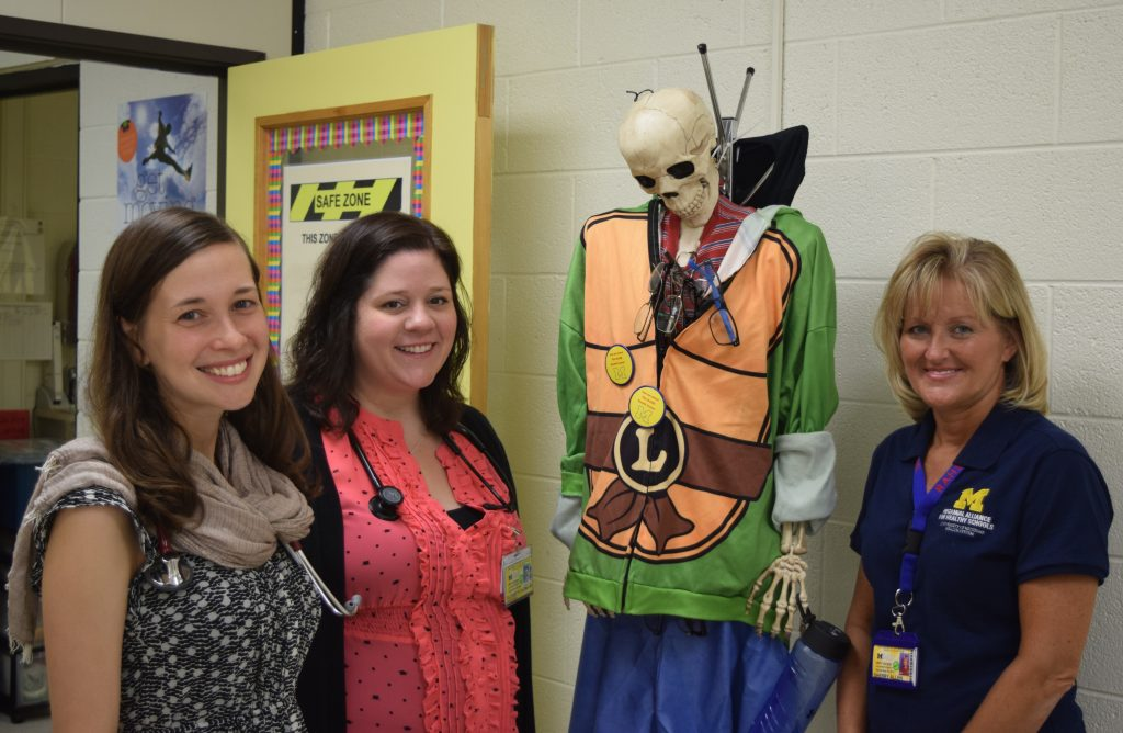 3 U of M RAHS Clinic staff members and a skeleton dressed in a halloween costume at Scarlett Middle School