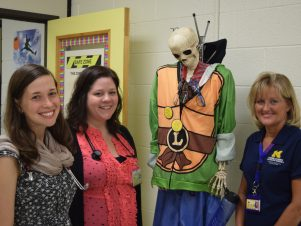 3 staff members at the University of Michigan RAHS Clinic at Scarlett Middle School stand next to a skeleton wearing a Halloween costume