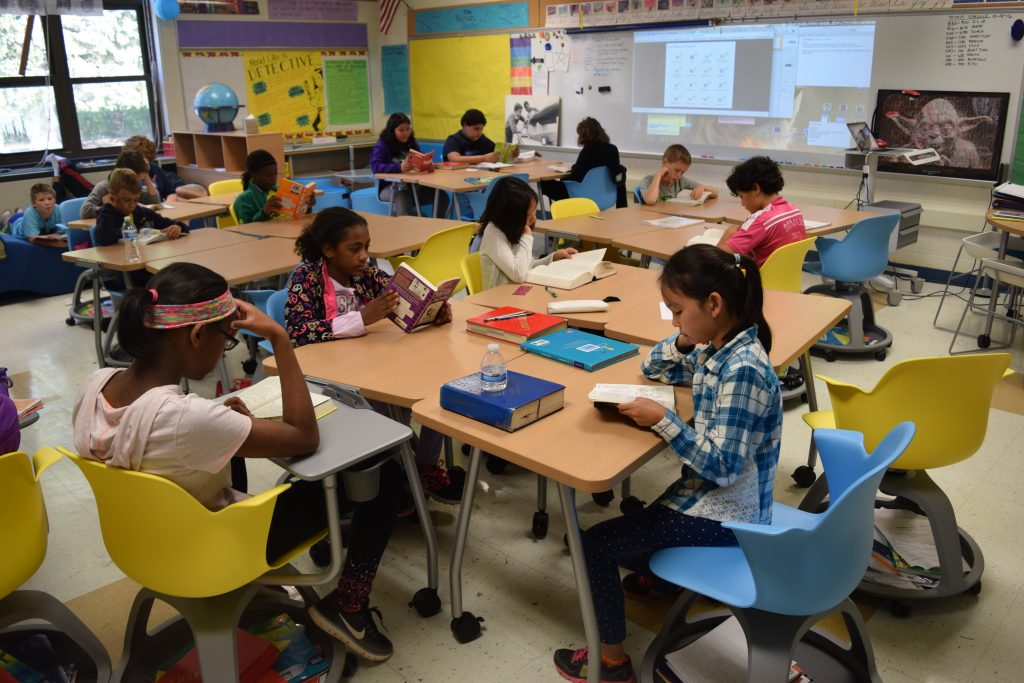 5th graders sitting in colorful chairs at new desks reading