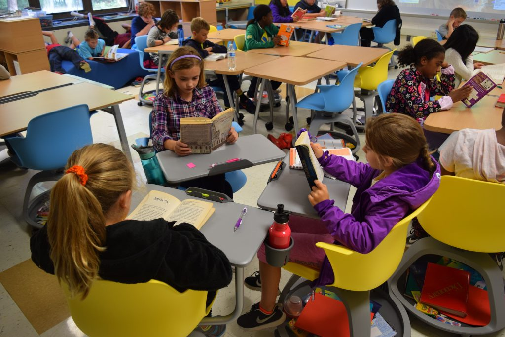 Three 5th grade girls read at new desks