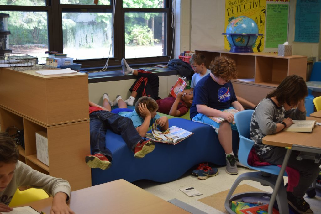 5th grade boys lie on a wavy couch reading books
