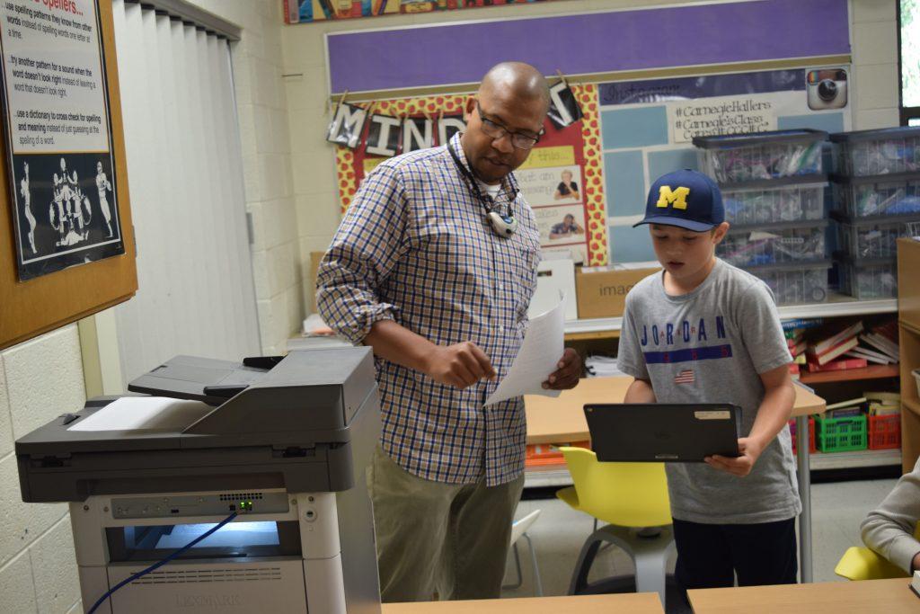 Teacher Ralph Carnegie talks with a 5th grader