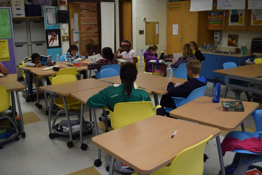 5th graders sitting at colorful chairs reading at new desks