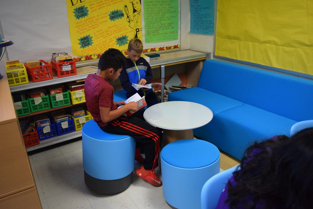 Two 5th graders reading on stools next to a couch