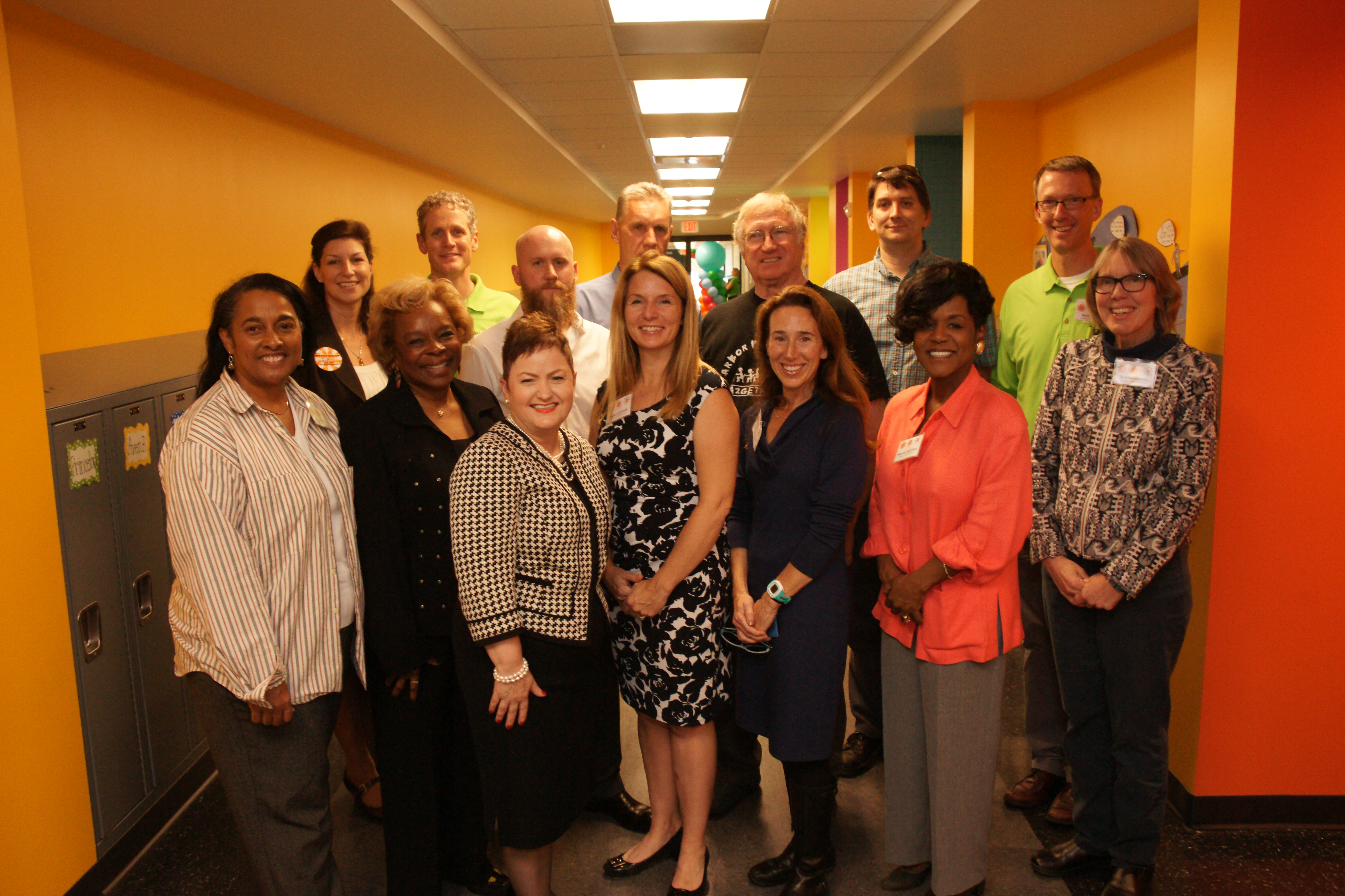 The AAPS school board and others standing in a bright hallway that's the expansion of Mitchell Elementary