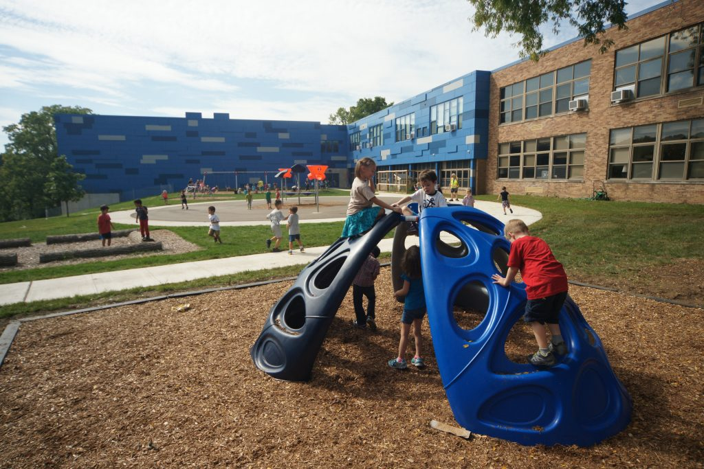 young kids climbing on a blue play structure