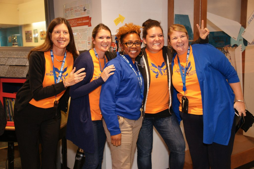 Several female teachers and staff members from A2 STEAM wearing orange shirts.