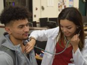 A female student with a stethoscope checks the heart beat of a male student.