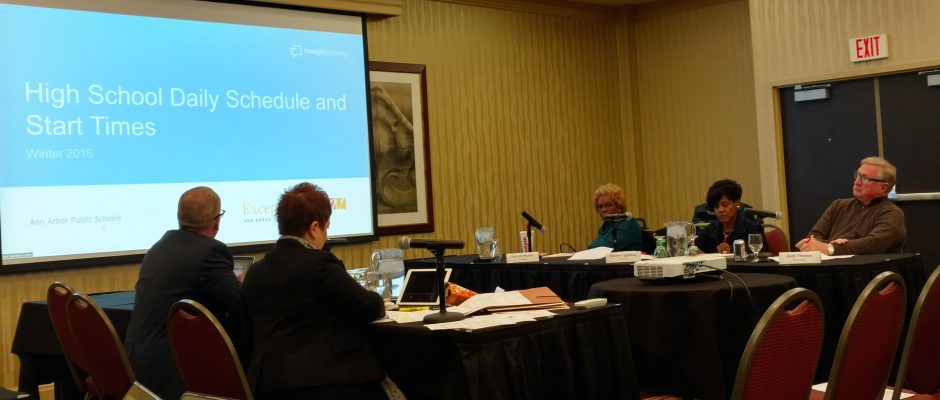 The AAPS BOE Performance committee in a hotel meeting room with a screen in the background highlighting high school start times as the topic of the meeting.