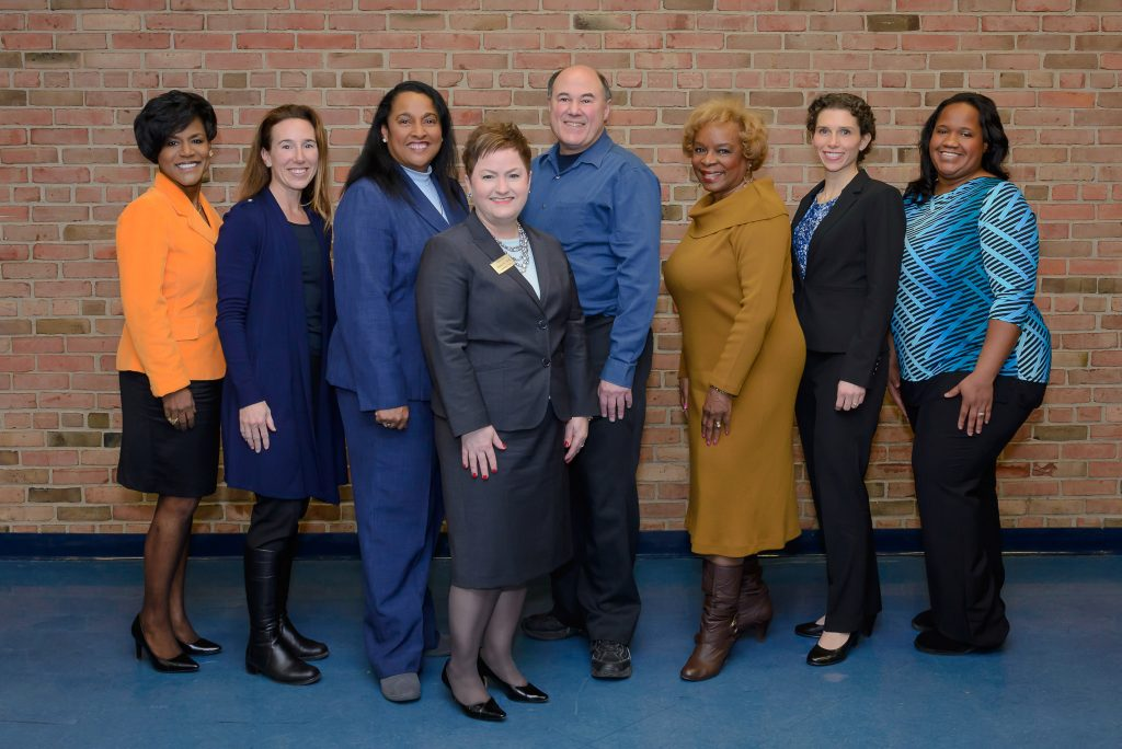 The seven members of the AAPS Board of Education and Superintendent Jeanice Swift stand in front of a brick wall.
