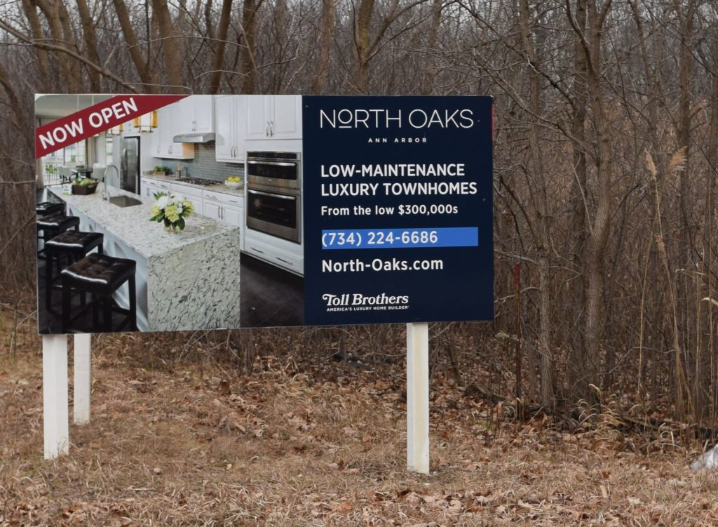 A sign in front of woods announcing the upcoming North Oaks townhouse development