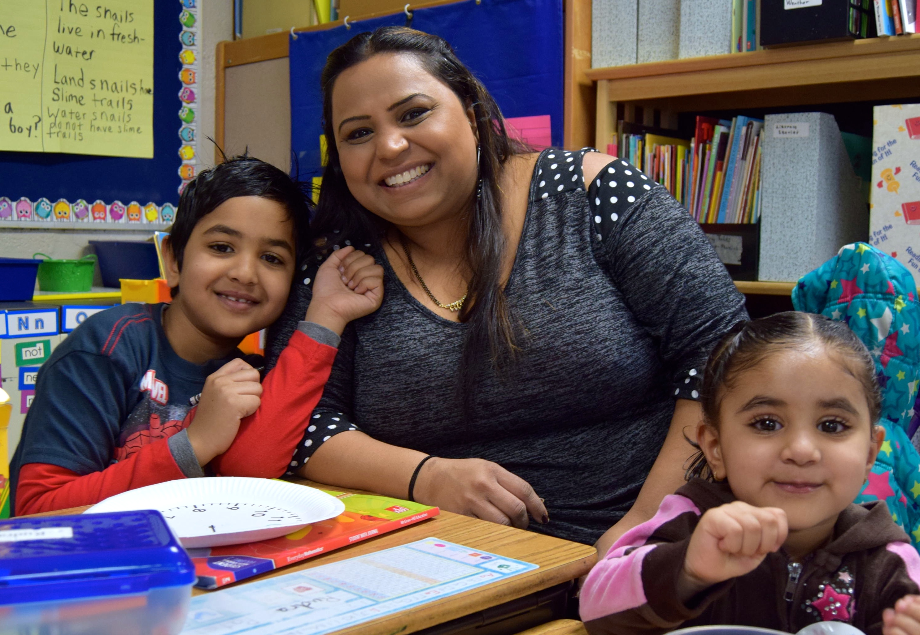 A mother and her two children in a bright school room setting.