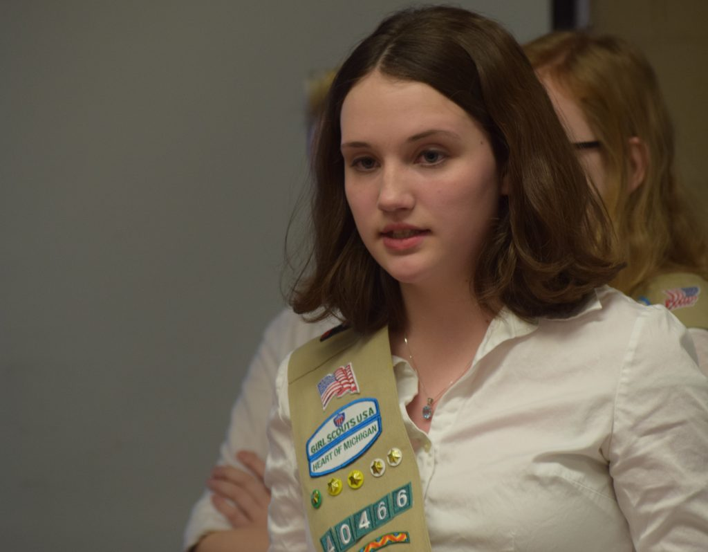 A 9th grade brunette wearing a girl scout sash talks to the committee.