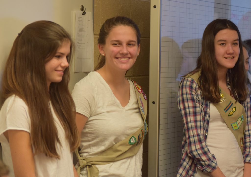 3 ninth grade girl scouts are smiling while the committee talks about their research