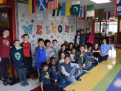 An Allen Elementary 5th grade class stands and kneels in front of a welcome sign