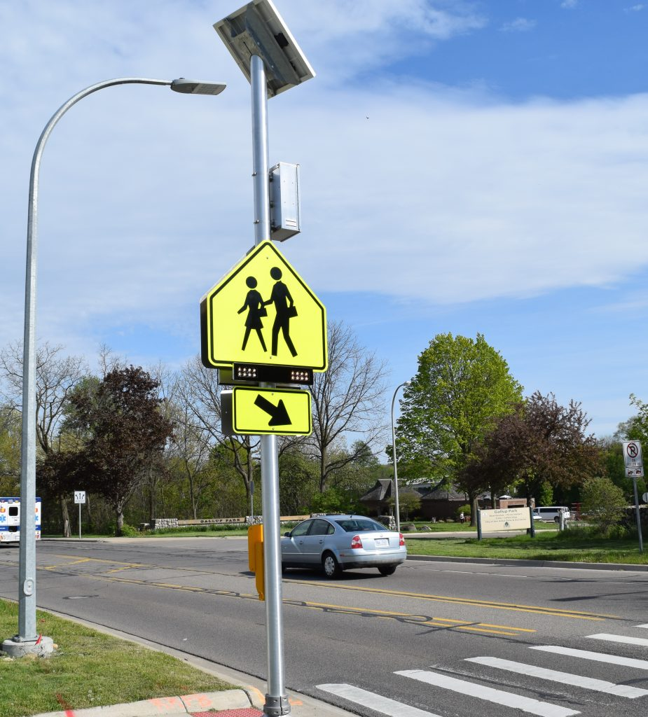 A school crossing sign with a flashing light next to a 3 lane stretch of Fuller