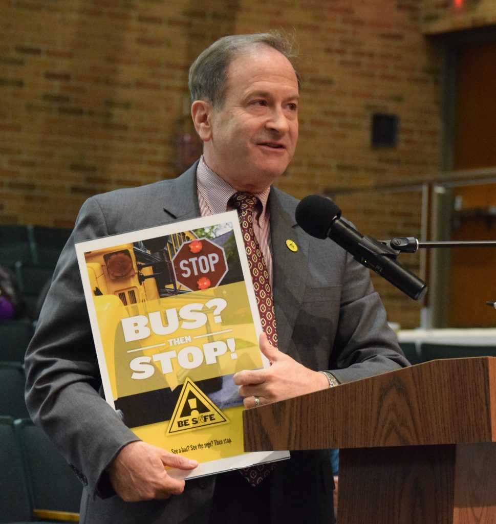 Ann Arbor City Administrator Howard Lazarus holding a poster with a school bus and the message to stop