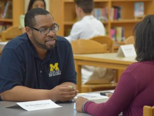 An African-American male wearing a blue shirt sits at a table interviewing an 8th grade student