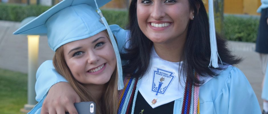A pair of girls wearing Skyline caps and Gowns celebrate after graduation