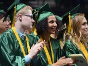 A group of Huron grads clap during the Commencement Address