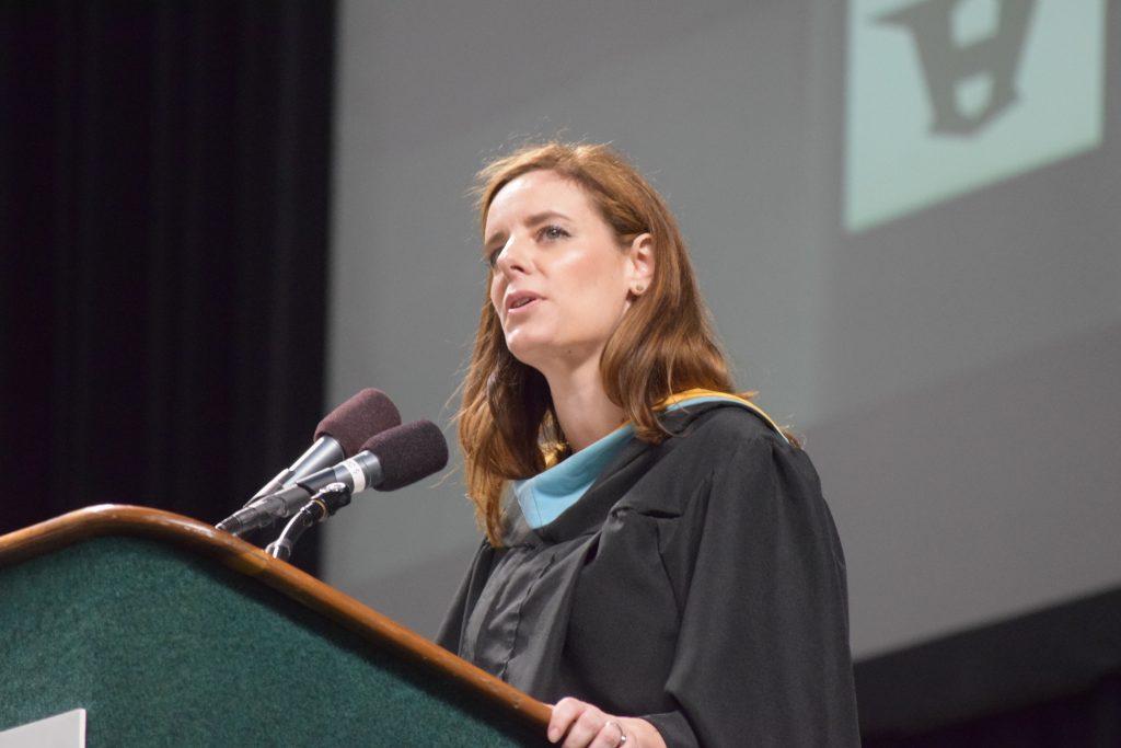 Huron Social Studies teacher Sarah Roldan-Dodson talking at a podium in a graduation gown