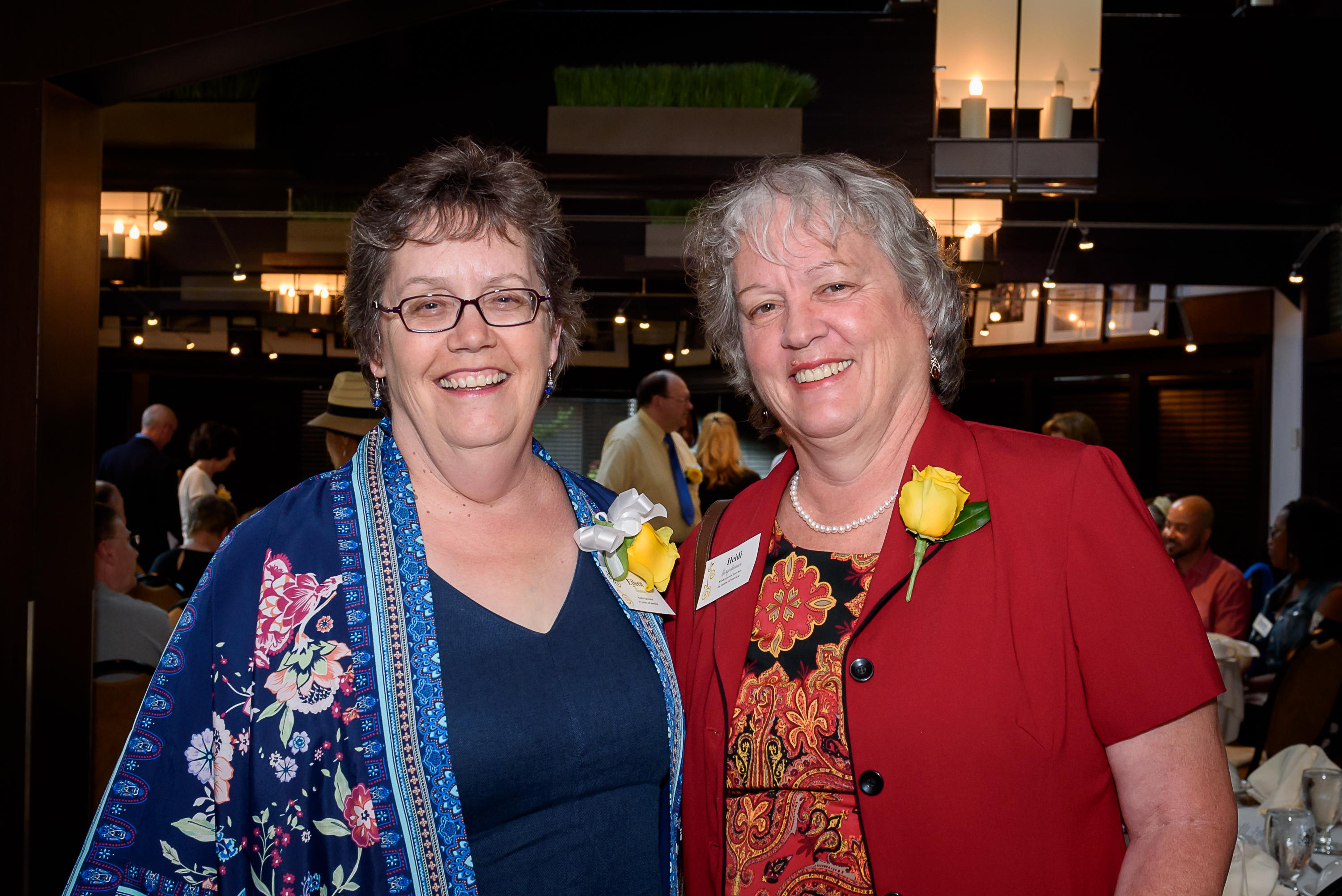 Two recent AAPS retirees wearing yellow rose bouquets at the Retirement Celebration
