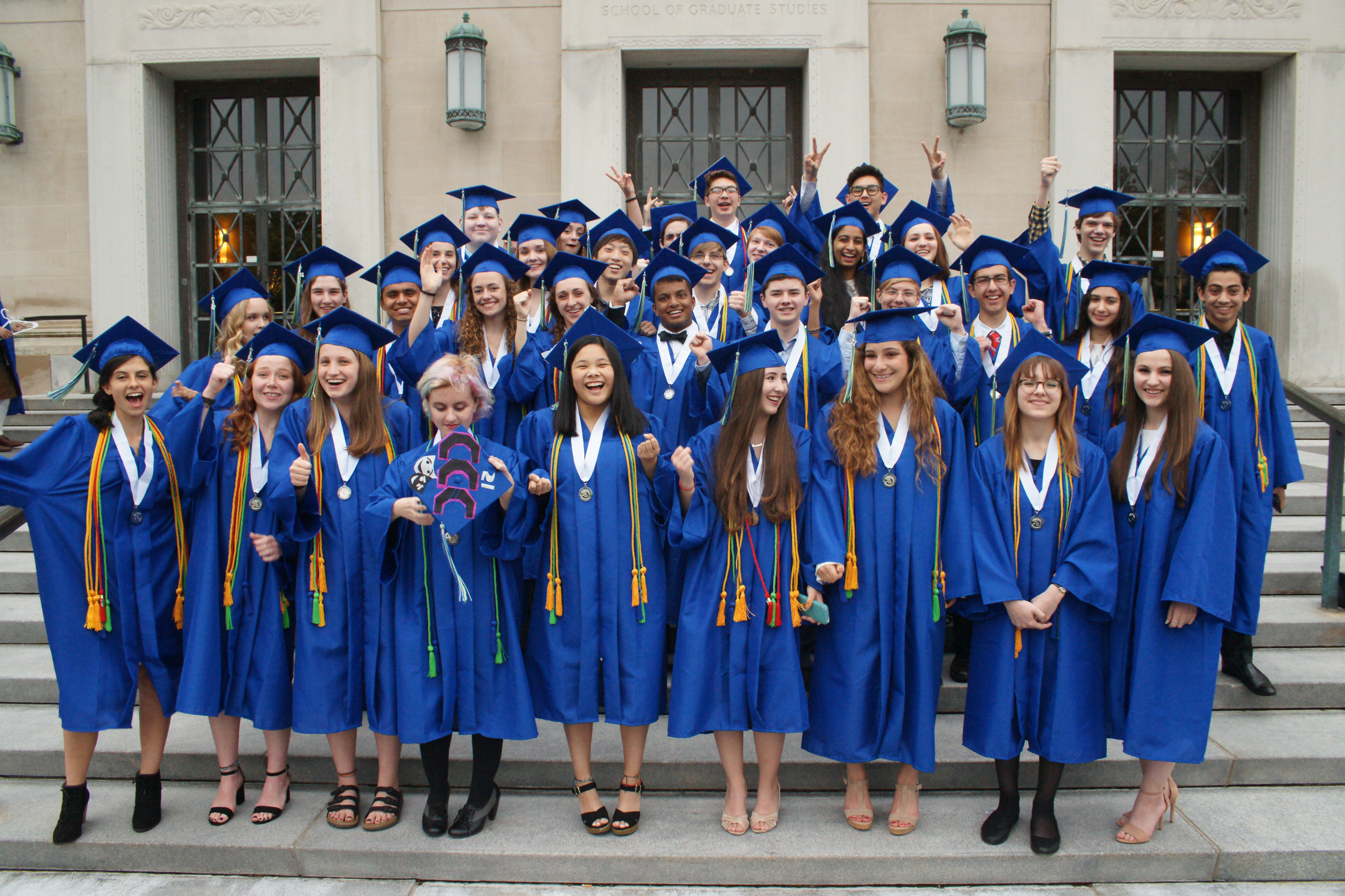 33 Washtenaw International High School graduates from Ann Arbor Public Schools wearing caps and gowns.