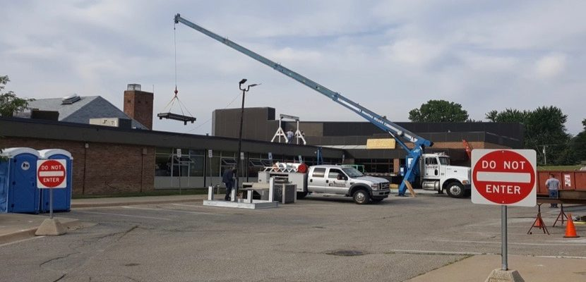A construction crane lifting a large piece of metal onto the roof of Allen Elementary School