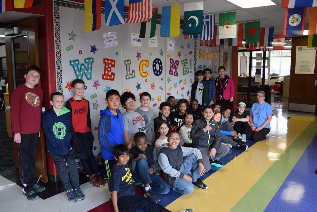 A group of Allen Elementary students in front of a sign saying Welcome Home.