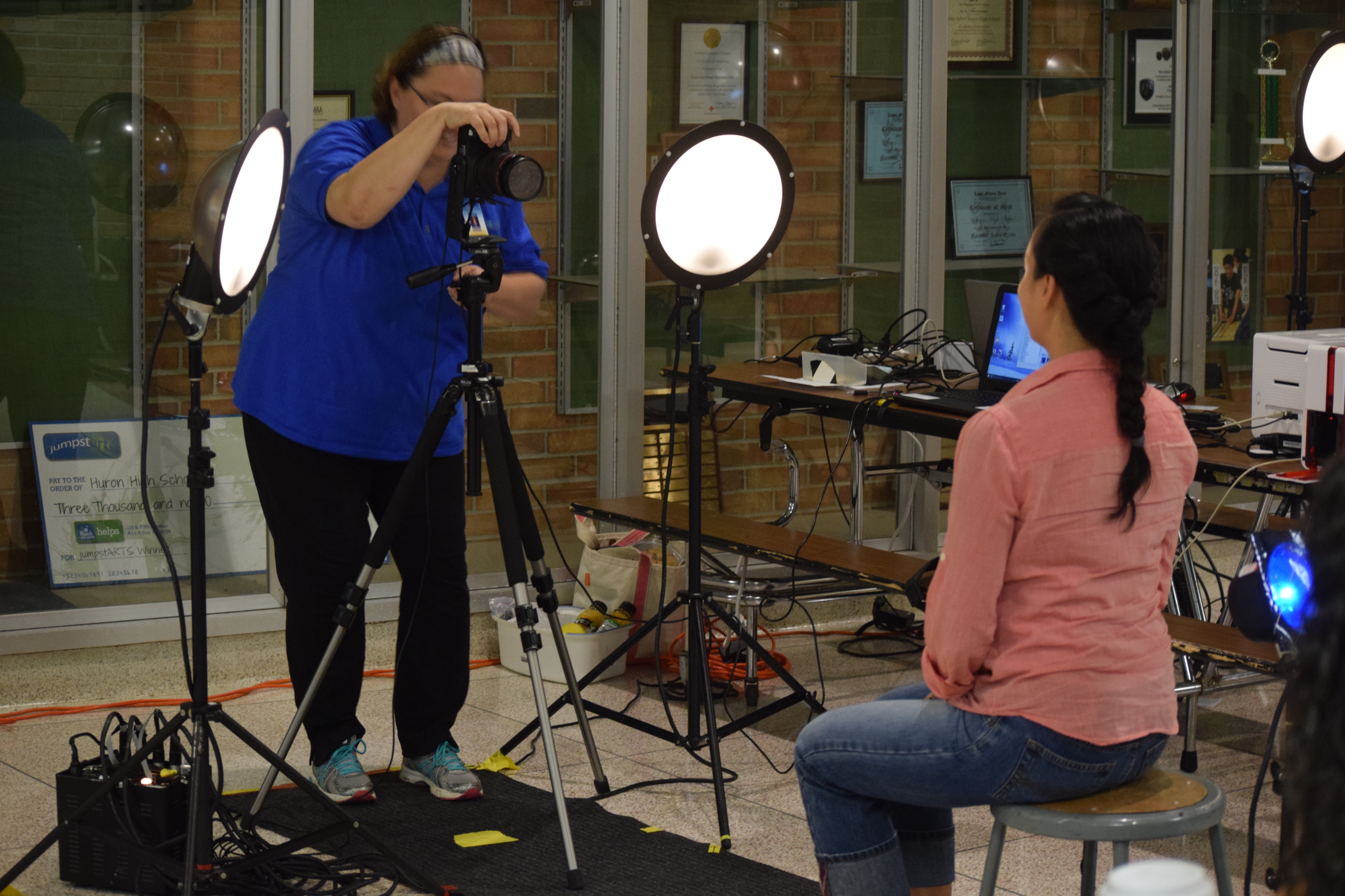 A photographer behind a camera next to bright lights is taking a photo of a female Huron staff member