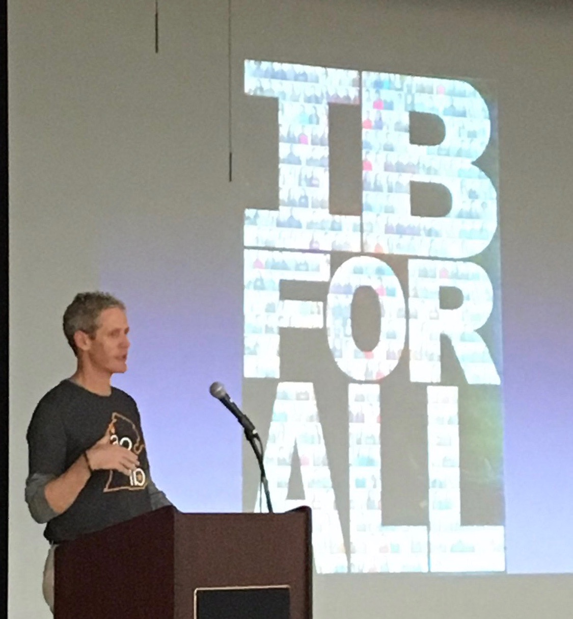 Kevin Karr stands at a podium with the screen behind saying IB For ALL